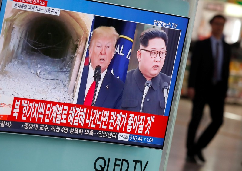 A man walks past a TV broadcasting a news report on a cancelled summit between the U.S. and North Korea, in Seoul