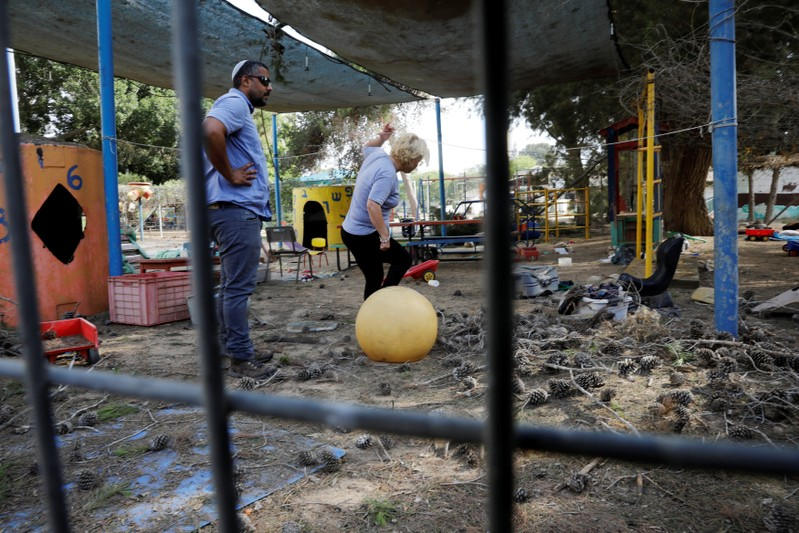 People stand in a kindergarten yard damaged by mortar shells fired from the Gaza Strip that landed near it, in a Kibbutz on the Israeli side of the Israeli-Gaza border