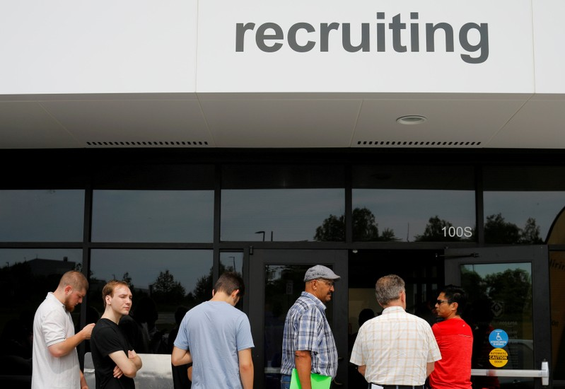 FILE PHOTO: Job seekers line up to apply during