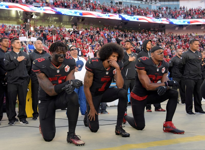 FILE PHOTO: San Francisco 49ers outside linebacker Harold, quarterback Kaepernick and free safety Reid kneel in protest during the playing of the national anthem before a NFL game against the Arizona Cardinals in Santa Clara