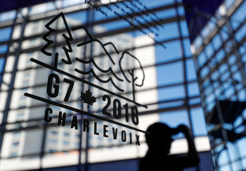 A man walks past the Charevoix G7 logo at the main press center ahead of G7 Summit in Quebec