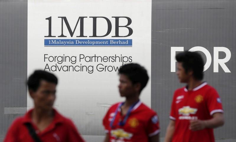 FILE PHOTO: Men walk past a 1 Malaysia Development Berhad (1MDB) billboard at the fund's flagship Tun Razak Exchange development in Kuala Lumpur