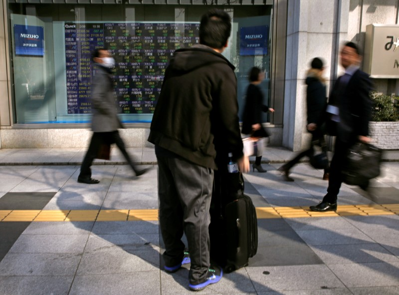 A man looks at an electronic stock quotation board outside a brokerage in Tokyo
