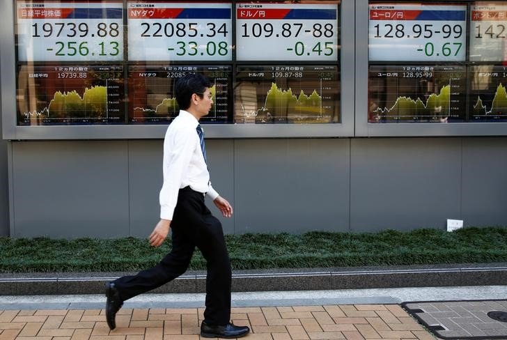 FILE PHOTO: A man walks past electronic boards showing Japan's Nikkei average, the Dow Jones Industrial Average and foreign exchange rates outside a brokerage at a business district in Tokyo