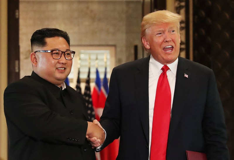 U.S. President Donald Trump and North Korea's leader Kim Jong Un shake hands after signing documents during a summit at the Capella Hotel on the resort island of Sentosa, Singapore