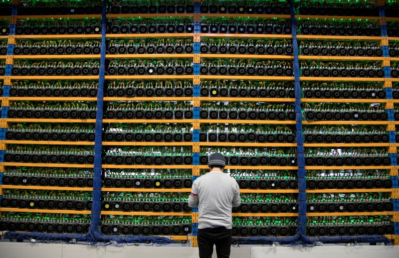 FILE PHOTO: A worker checks the fans on miners at the cryptocurrency farming operation Bitfarms in Farnham Quebec