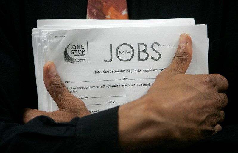 FILE PHOTO: Man carrying a stack of job listings listens to a discussion at the One Stop employment center in San Francisco