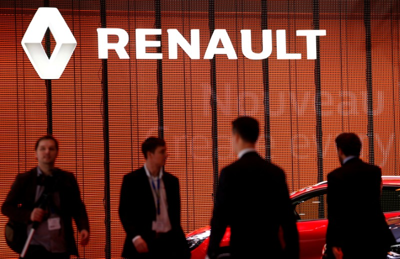 FILE PHOTO: Visitors walk past a Renault logo on the car maker's booth during the second media day of the 86th International Motor Show in Geneva