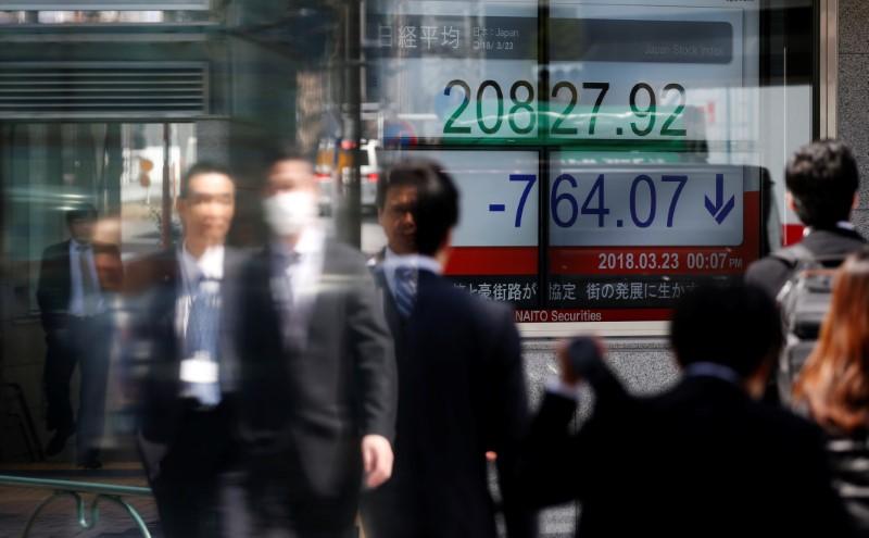 People walk past an electronic board showing Japan's Nikkei average outside a brokerage in Tokyo
