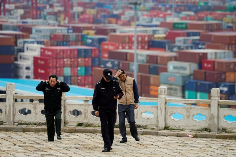 FILE PHOTO: Security guards walk in front of containers at the Yangshan Deep Water Port in Shanghai