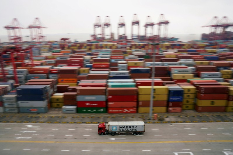 FILE PHOTO: A container truck moves past containers at the Yangshan Deep Water Port in Shanghai