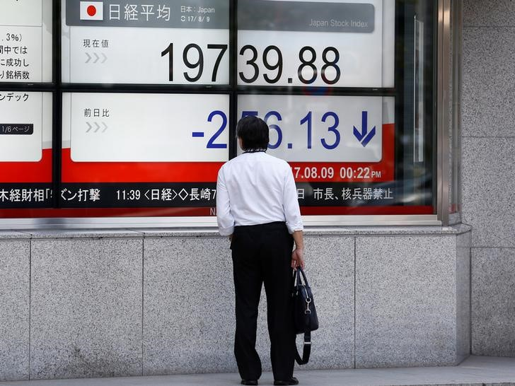 FILE PHOTO: A man looks at an electronic board showing Japan's Nikkei average outside a brokerage at a business district in Tokyo