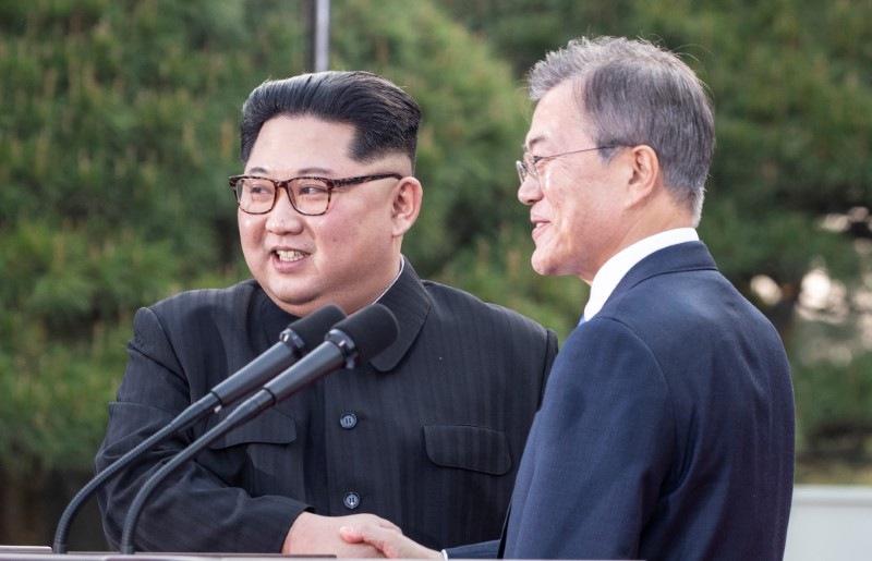 South Korean President Moon Jae-in and North Korean leader Kim Jong Un shake hands at the truce village of Panmunjom