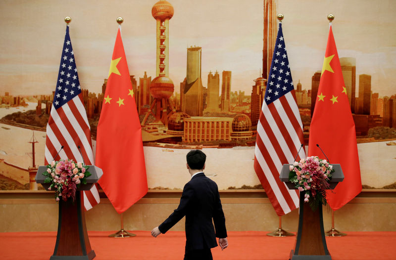 FILE PHOTO: A staff member walks past U.S. and Chinese flags placed for a joint news conference in Beijing