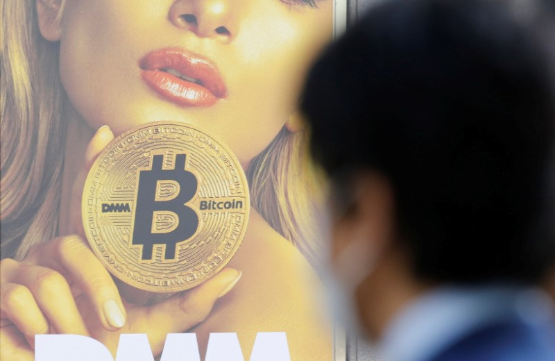 FILE PHOTO: A man stands near an advertisement of a cryptocurrency exchange in Tokyo
