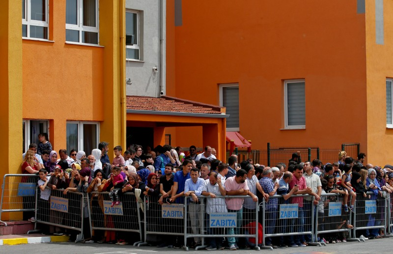Supporters of Turkish President Tayyip Erdogan wait for him to arrive at a polling station in Istanbul