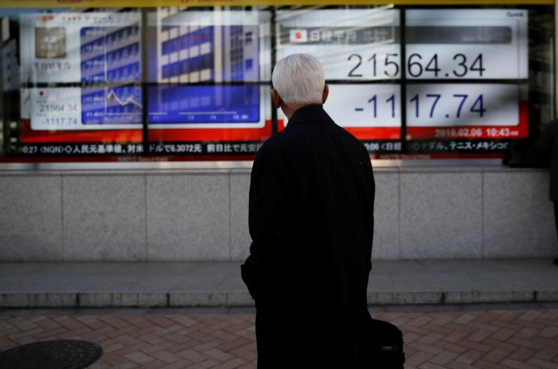 A man looks at an electronic board showing Japan's Nikkei average outside a brokerage in Tokyo