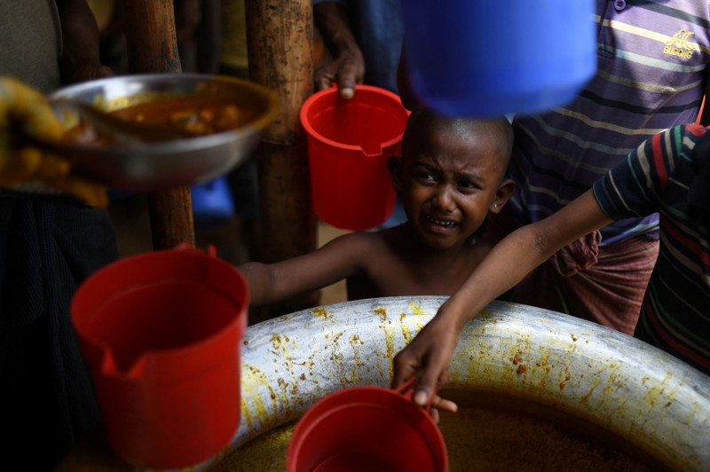 FILE PHOTO: FILE PHOTO: Rohingya refugee child waits for rations