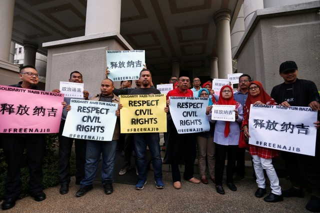 Supporters of former Malaysian prime minister Najib Razak hold up signs, ahead of his arrival to court in Kuala Lumpur