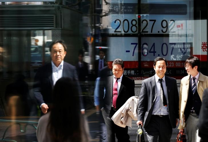 People walk past an electronic board showing Japan's Nikkei average outside a brokerage in Tokyo