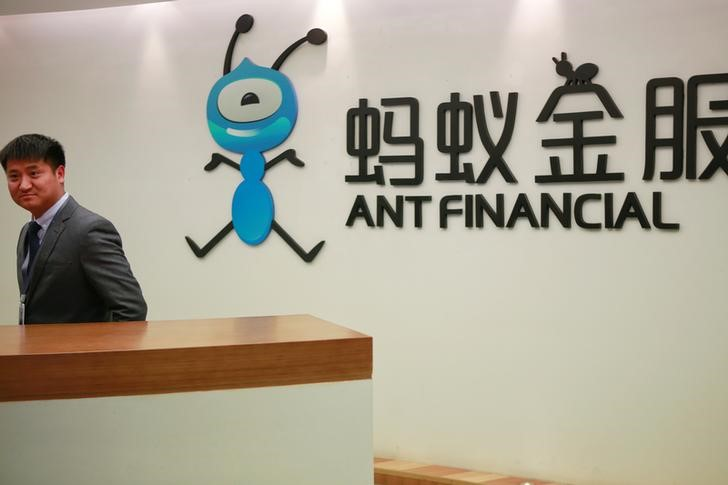 Employee stands next to the logo of Ant Financial Services Group at its headquarters in Hangzhou