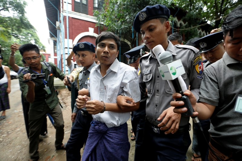 Detained Reuters journalist Kyaw Soe Oo is escorted by police while leaving Insein court in Yangon