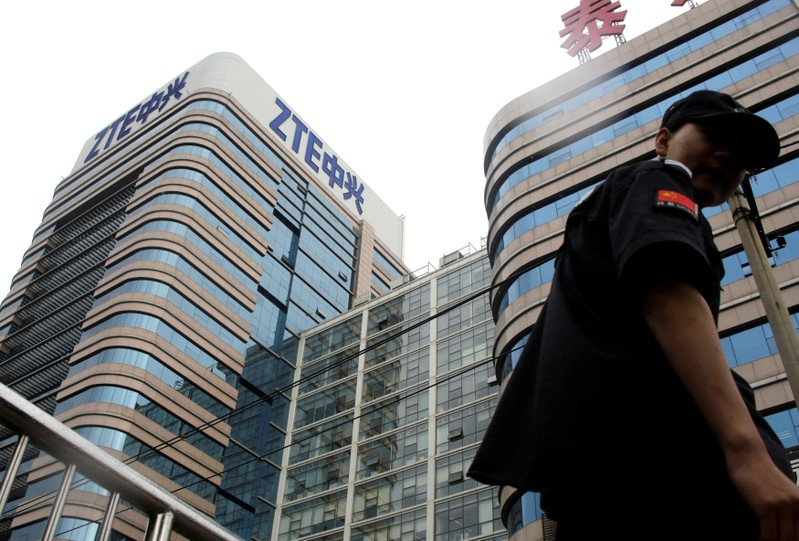 FILE PHOTO: A security guard walks past a building of ZTE Beijing research and development center in Beijing