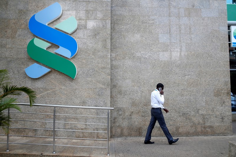 A man walks past a logo of the Standard Chartered Kenya bank in their main office in Nairobi,