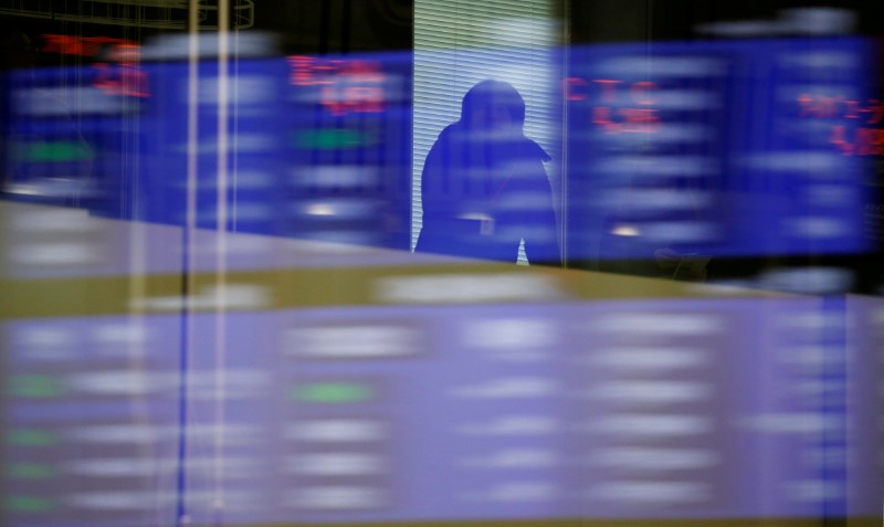 FILE PHOTO: A visitor is seen as market prices are reflected in a glass window at the TSE in Tokyo
