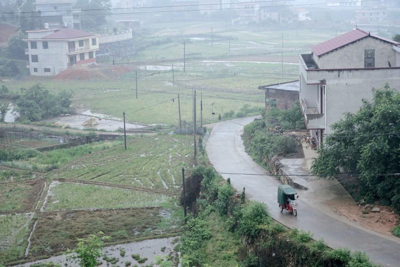 Man rides past houses at Furong village