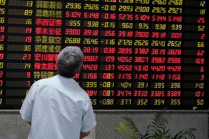 A man looks at an electronic board showing stock information at a brokerage house in Shanghai, China