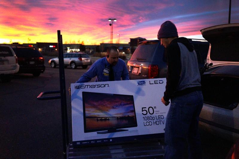 FILE PHOTO: A Walmart employee helps a customer load a 50
