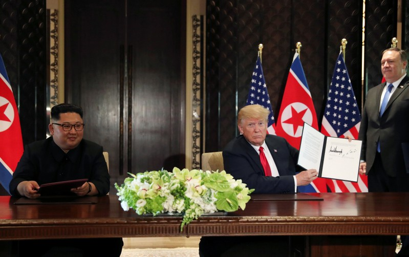 FILE PHOTO: U.S. President Donald Trump shows the document, that he and North Korea's leader Kim Jong Un signed at their summit in Singapore