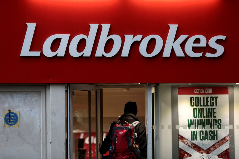FILE PHOTO: A man walks into a branch of a Ladbrokes bookmaker in London