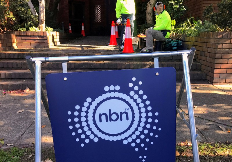FILE PHOTO: Workers install cables for the Australian National Broadband Network at an apartment block in Sydney