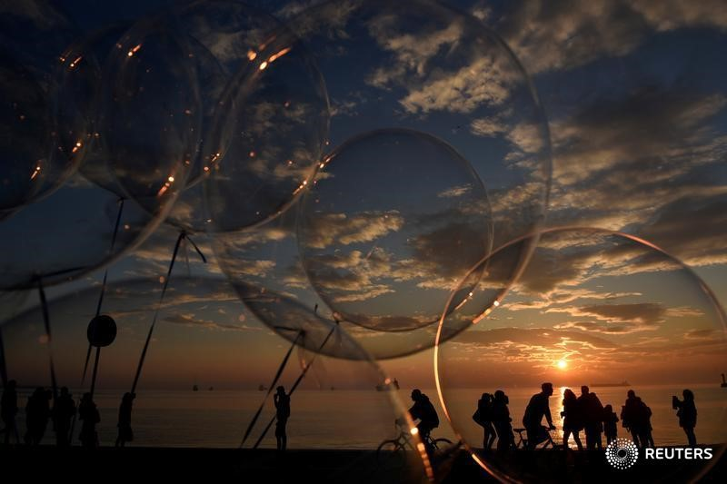 People are seen through balloons as they make their way at the seaside promenade of the northern port city of Thessaloniki