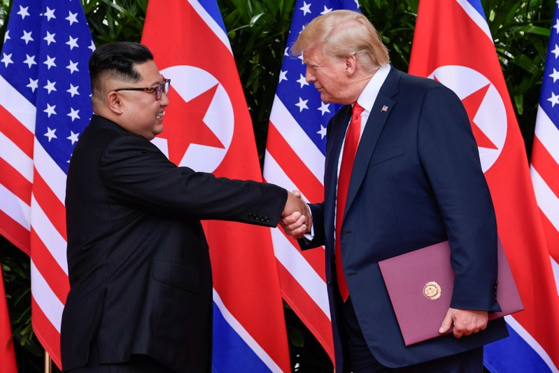 FILE PHOTO - U.S. President Donald Trump and North Korea's leader Kim Jong Un shake hands during the signing of a document after their summit at the Capella Hotel on Sentosa island in Singapore