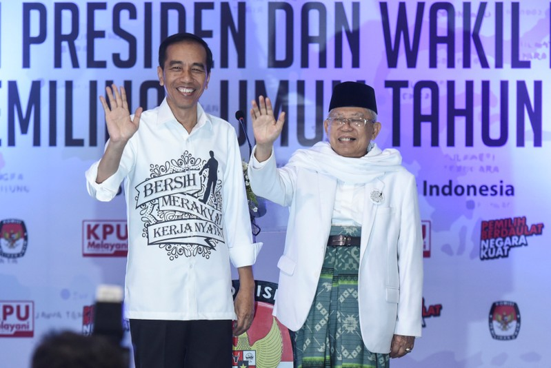Indonesian President Joko Widodo and his running mate for the 2019 presidential election Islamic cleric Ma'ruf Amin wave after registering for the election at the General Election Commission in Jakarta