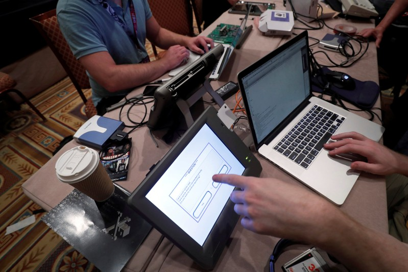 FILE PHOTO: Hackers try to access and alter data from an electronic poll books in a Voting Machine Hacking Village during the Def Con hacker convention in Las Vegas
