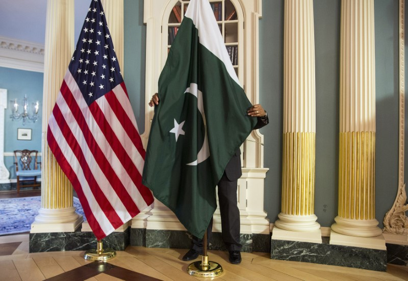 A State Department contractor adjust a flag before a meeting between U.S. Secretary of State Kerry and Pakistan's Interior Minister Khan on the sidelines of the White House Summit on Countering Violent Extremism at the State Department in Washington