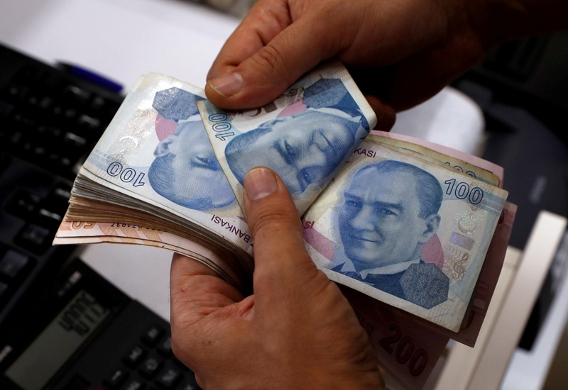 FILE PHOTO: A money changer counts Turkish lira banknotes at a currency exchange office in Istanbul