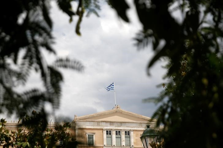 A Greek flag flutters atop the parliament building in Athens