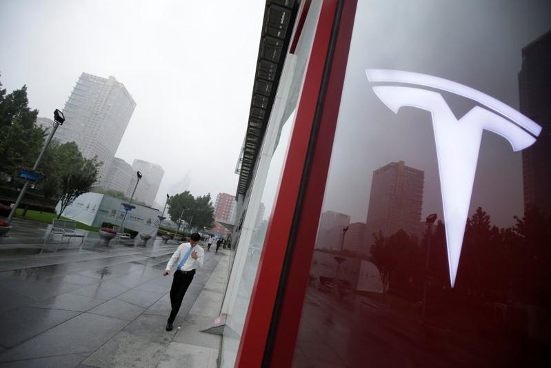 A man walks near a logo of Tesla outside its China headquarters in Beijing