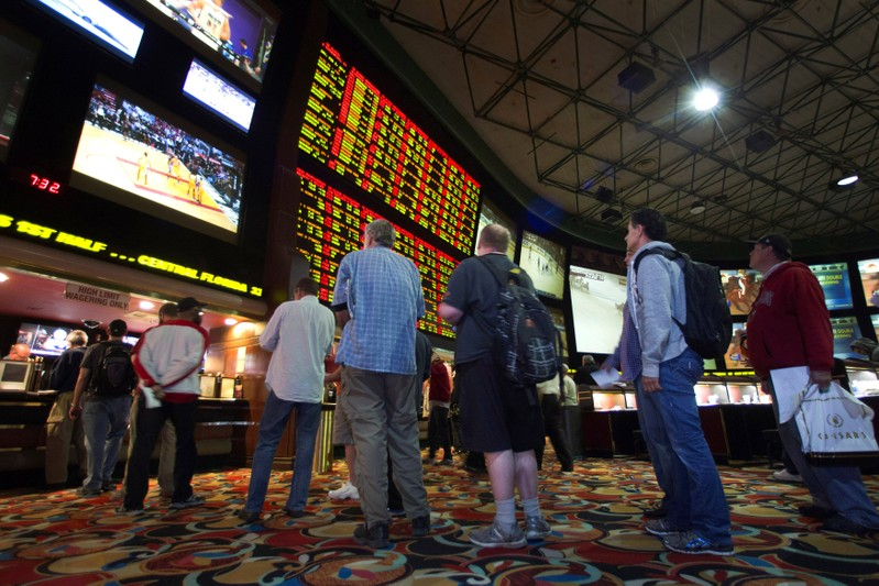 FILE PHOTO: People wait in line to place bets after Super Bowl XLVIII proposition bets were posted at the Las Vegas Hotel & Casino Superbook in Las Vegas
