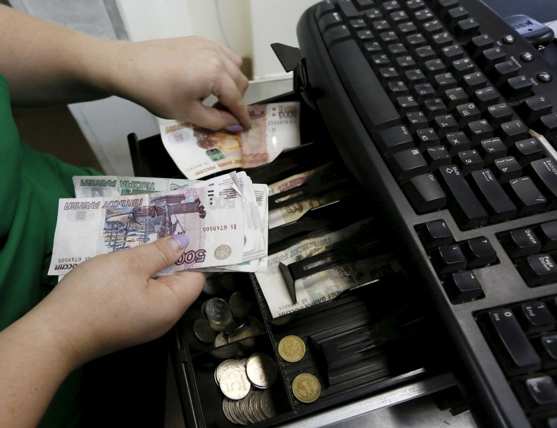 A vendor places Russian rouble banknotes at a grocery shop in Krasnoyarsk