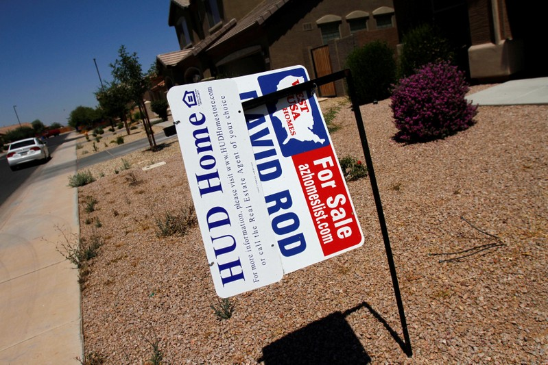 FILE PHOTO: Real estate for sale and Housing and Urban Development signs are displayed outside a home in Chandler Heights, Arizona