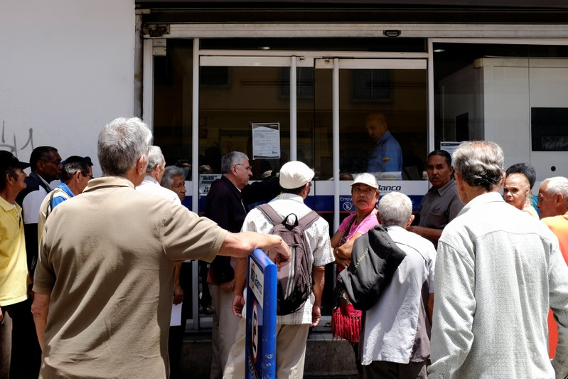 People line up to withdraw a part of their pensions outside a bank branch in Caracas