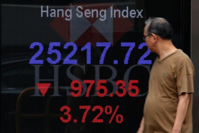 A man walks past a panel displaying the Hang Seng Index during morning trading in Hong Kong