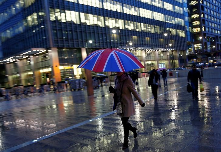FILE PHOTO: Workers walk in the rain at the Canary Wharf business district in London