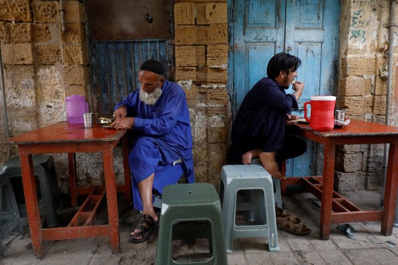 Laborer eat their lunch at a makeshift stall along a sidewalk in Karachi,